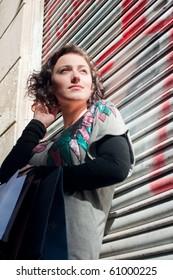 Girl with shopping bags at graffiti wall