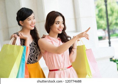 Girl with shopping bags pointing at something to her friend