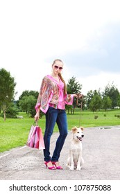 Girl with shopping bags standing on the track with her puppy