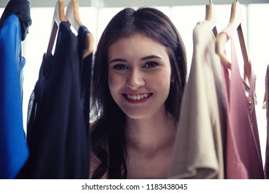 girl shopping cloth at clothing store. she chooses best dress for herself. Beautiful smiling on her face make the world happier.