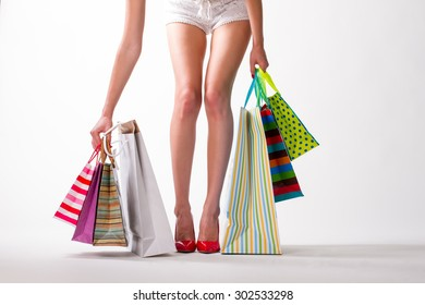 Girl with shopping. Leggy lady in red shoes.