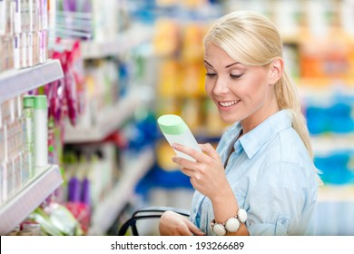 Girl at the shopping mall choosing cosmetics among the great variety of products. Concept of consumerism, retail and purchase
