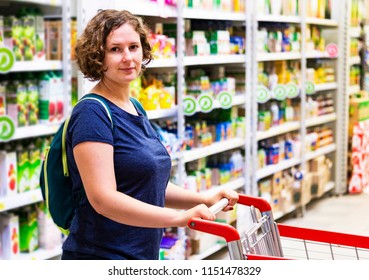 The girl in shopping mall. The customer with a grocery cart in store. The woman chooses products in a supermarket. The housewife,female  against the background of products