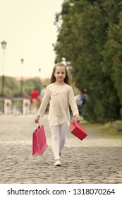Girl shopping on calm face carries shopping bags, urban background. Kid girl with long hair fond of shopping. Shopping concept. Girl likes to buy clothes. Fashionista girl with pink bags