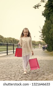 Girl shopping on calm face carries shopping bags, urban background. Kid girl with long hair fond of shopping. Fashionista girl with pink bags. Shopping concept. Girl likes to buy clothes