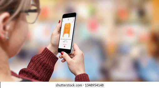 Girl shopping online on her phone, blurred store in background with free space