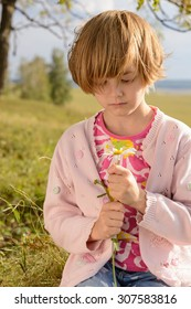 The girl with short blond hair holding a daisy