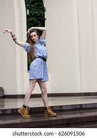 girl in a short dress and boots dancing in the city