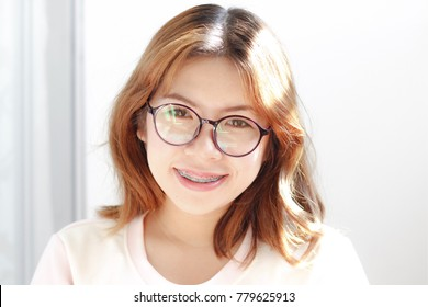 Girl with short hair brown,white skin,Asia,pink lips. Wearing glasses, braces.