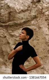 Girl with a short haircut pixie on the background of the textural rock