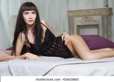 Girl in short peignoir lying on the bed in the bedroom