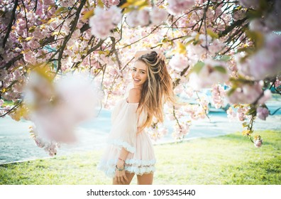 Girl in short pink dress enjoying sunny day in botanical garden. Female playing with long gorgeous blond hair, beauty and hair care products. Sexy woman posing under blooming cherry blossom tree.