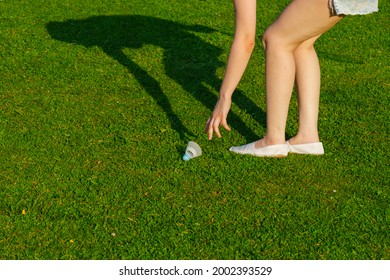 Girl in shorts playing badminton bent over to pick up shuttlecock from lawn
