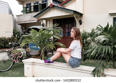 Girl in shorts sitting by the villa