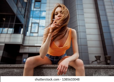 Girl in shorts Smoking on the street.