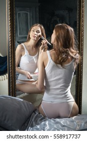 Girl in shorts and a T-shirt in the morning near the mirror