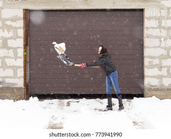 Girl with a shovel cleans the snow