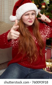 Girl show gesture of a gun. Dressed in retro red sweater and santa hat. Home interior with christmas decoration, fir tree and gifts. New year eve and winter holiday concept.