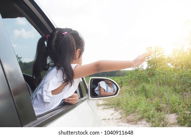 The girl show hand from the car waving to nature.