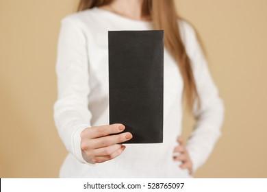 Girl showing blank black flyer brochure booklet. Leaflet presentation. Pamphlet hold hands. Woman show clear offset paper. Sheet template. Booklet design sheet display read first person.