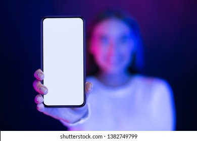 Girl showing blank smartphone screen over neon studio background, blue and pink lights