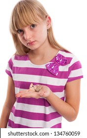 Girl showing her hearing aid in front of a white background.