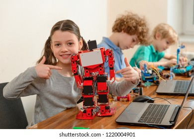 Girl showing her robot and pointing her finger. Proud student of her project. Growing smart kids with STEM education.