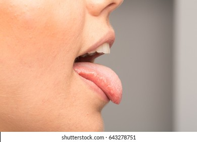 Girl showing her tongue out on grey background