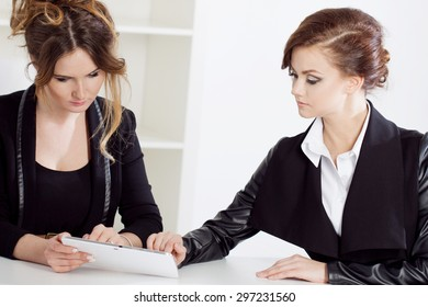Girl showing something to her colleague, work in the office
