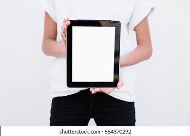 Girl showing tablet. On a white background. Close up.