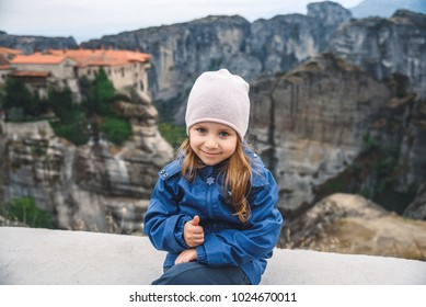 girl showing thumb up sitting on hill at meteora in Greece