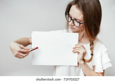Girl showing white paper blank and pointing with pen
