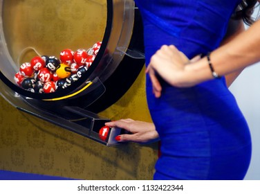 A girl shows a ball in a drum lottery.