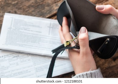 girl shows an empty wallet without money on the background of the tax return