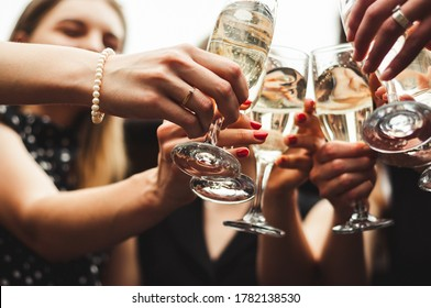 The girl shows an engagement ring on her finger. Happy wedding day. Pre-wedding party. Chilling Together. Girls party. Glasses of champagne