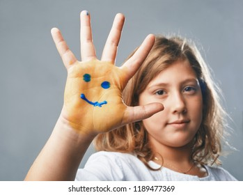 the girl shows hand with drawn emoticons