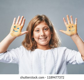 the girl shows hands with drawn emoticons