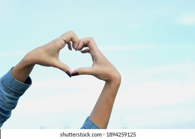 girl shows hands heart sign on sky background
