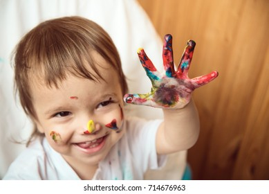 A girl shows her hand dirty with paints