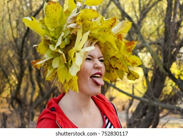 The girl shows her tongue. Girl in a red jacket with a wreath of yellow autumn leaves. The Queen of Autumn. Miss autumn. Autumn Walk