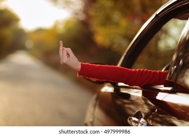 The girl shows obscene gesture from a car
