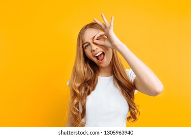 girl shows OK, on yellow background, woman shows gesture