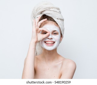 Girl shows a sign of class in a hygienic mask a white background