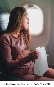 Girl is sick in the airplane and seating with paper pocket