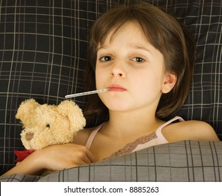 A girl sick in bed with stuffed bear for comfort