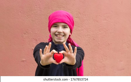 girl sick with cancer with red heart in her hands