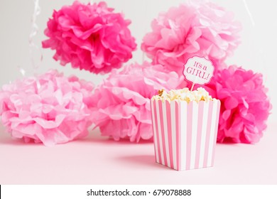 It's a girl sign in a popcorn bag at the baby shower party.  Paper flowers background. Baby shower celebration concept. Festive party background. Horizontal