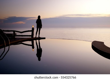 Girl silhouette by the swimming pool with sea behind at sunset