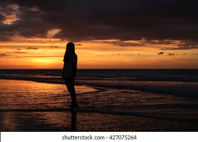 A girl silhouette during sunset at the beach.