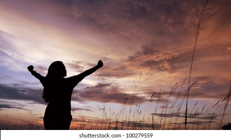 Girl in silhouette with open arms freedom feeling over sunset background